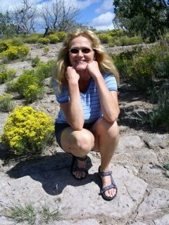A color photograph of memoir editor and author Lisa Dale Norton while on a hike in the mountains outside Santa Fe, New Mexico. She is wearing blue shorts, a blue-and-white stripped short-sleeved top, and sandals. She is crouching over her heels with elbows on her knees smiling broadly at the camera. She sports John Lennon-like sunglasses. Her long, reddish-blonde hair flows over her shoulders. Around her bunches of yellow flowers bloom amidst pinion pines and juniper trees. Blue skies and puffy white clouds fill out the horizon. Norton is one of America's foremost independent editors of memoir. She is a gifted story analyst and a compassionate and wise teacher of the art and craft of writing. Norton is the author of America's favorite handbook for writing memoir entitled Shimmering Images: A Handy Little Guide to Writing Memoir.