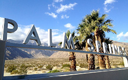 """A landscape photograph of the sign for Palm Springs, California, with blue sky and puffy white clouds behind it, and palm trees and blooming desert stretching into the distance with mountains on the far horizon. Palm Springs is the site of memoir author and editor Lisa Dale Norton's upcoming Feb. 4, 2018, writing workshop """"Writing the Best Memoir You Can,"""" sponsored by the Palm Springs Writers Guild."""